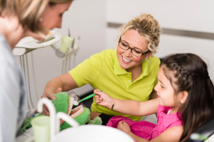 Kind lernt spielerisch die Zähne zu pflegen