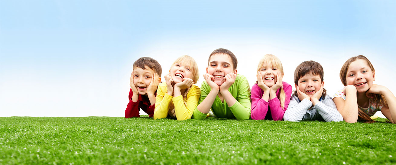 Lachende Kinder liegen nebeneinander auf einer grünen Wiese